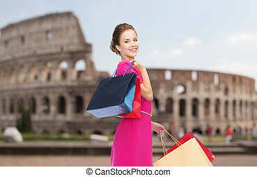happy woman with shopping bags over coliseum - people,...