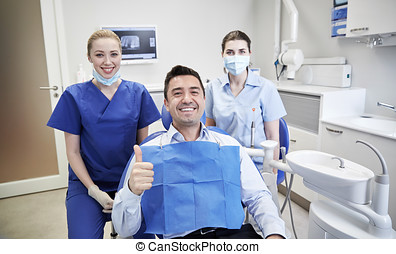 happy female dentists with man patient at clinic - people,...