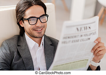 Pleasant smiling man reading newspaper - In whirlwind of...