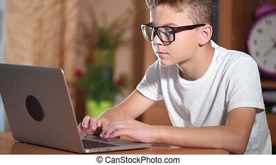 Teen boy working on laptop - Teen boy in glasses doing...