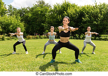 Delighted smiling women doing sport exercises outdoors. -...