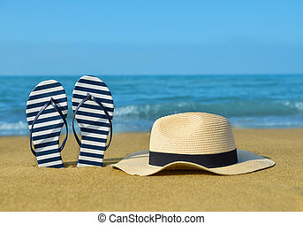 Flipflops and hat on sandy beach. - Flipflops and hat on a...