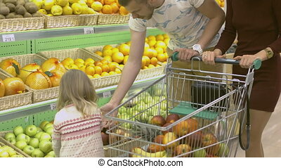 Family makes purchases in the supermarket Little girl...