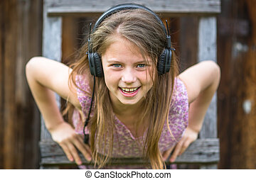 Naughty girl with headphones outdoors close-up portrait.