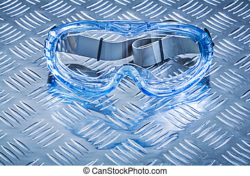 Multiple-purpose goggles on grooved metal background constructio