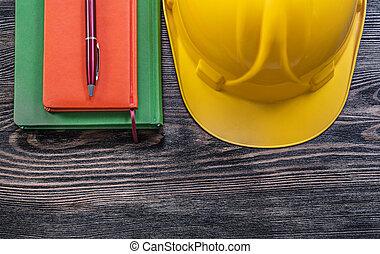 Note-books ballpoint pen protective building helmet on wooden bo