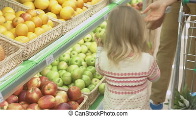 Family makes purchases in the supermarket - Family choosing...
