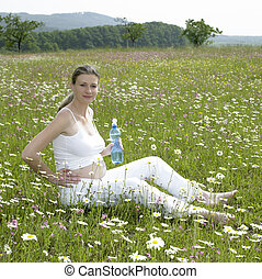 pregnant woman on meadow with bottle of  water