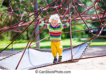 Little boy on a playground - Active little child playing on...