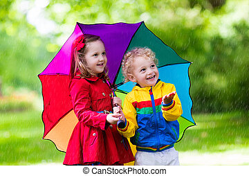 Kids playing in the rain under colorful umbrella - Little...