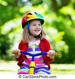 Little girl riding a tricycle - Cute girl wearing safety...