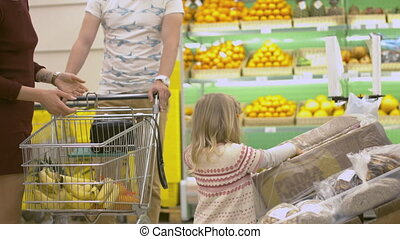 Family makes purchases in the supermarket. Little girl helps...