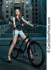 Girl on bicycle at night. - Woman biker in night city, sits...