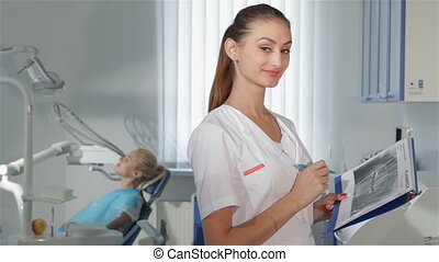 Female dentist poses at the dental clinic - Attractive...