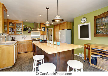Kitchen room interior with large wooden kitchen island, white built in fridge and green walls