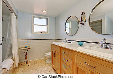 Bright bathroom in blue tones with cabinets and shower.