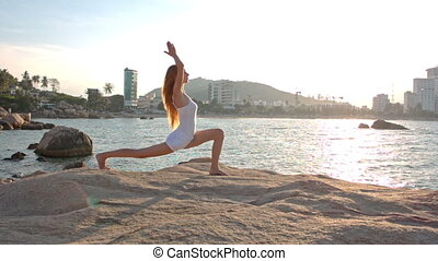 Blond Girl Stands in Yoga Pose Bent Leg on Rocky Beach -...