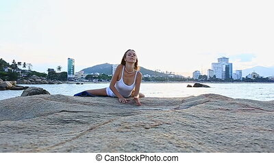 Blond Girl Lies down on Stone from Yoga Pose Lotus on Beach...