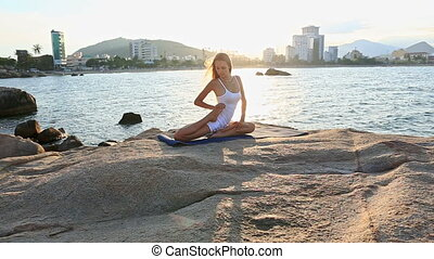 Blond Girl Sits in Yoga Foot on Waist on Rocky Beach - young...