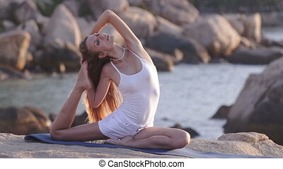 Blond Girl Sits Bends Backward to Foot in Yoga on Rocky...