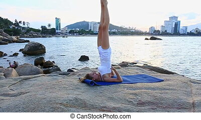 Blond Girl in Yoga Pose Shoulderstand on Stony Beach - young...