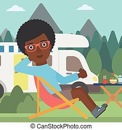 Woman sitting in chair in front of camper van - An...