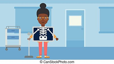Patient during x ray procedure - An african-american woman...