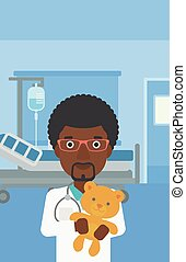 Pediatrician doctor holding teddy bear - An african-american...