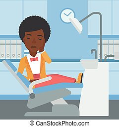 Woman suffering in dental chair. - An african-american young...