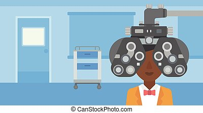 Patient during eye examination. - An african-american woman...