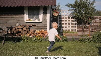 Happy Little Boy Running Around His Mom In The Garden
