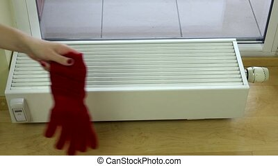 girl hand put red woolen gloves on radiator at home. - girl...