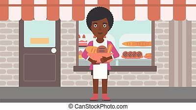 Baker holding basket with bakery products.