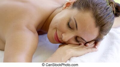 Woman with chin on folded towel smiles while laying on...