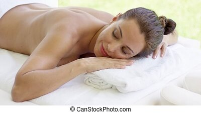 Naked woman relaxes on massage table with chin on hands over...