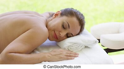 Woman smiles at camera while at spa on outdoor massage table...