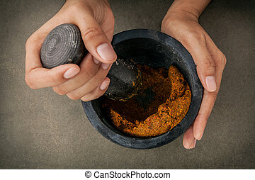 The Women hold pestle with mortar and and spice red curry...