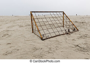 Rusted soccer goal on a beach with fishermen at sea on the...