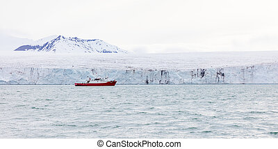 Expedition boat in front of a massive glacier - Expedition...