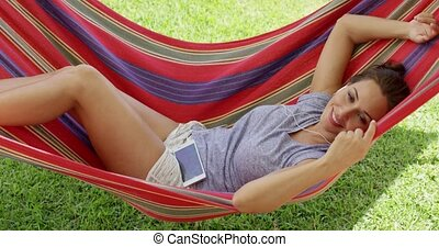 Happy young woman relaxing in a colorful hammock outdoors in...