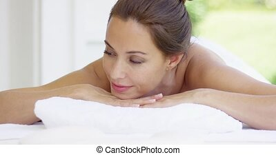 Woman smiles and relaxes on massage table on pleasant summer...