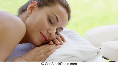 Woman with hair up in a bun rests on folded towel on spa...