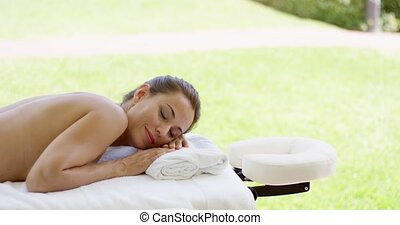 Naked woman on spa table closes her eyes while resting near...