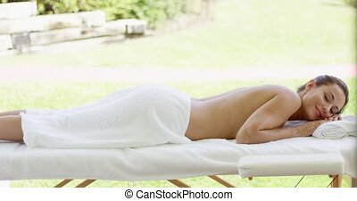 Woman only wearing towel rests on table in spa outdoors on...