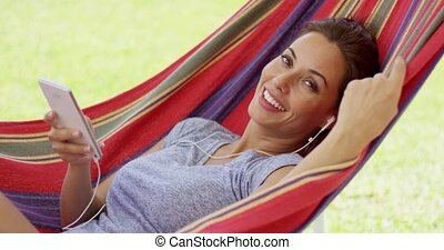 Happy young woman listening to music in a hammock outdoors...