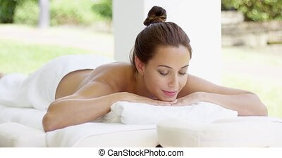 Naked woman on massage table smiles as she rests in outdoor...