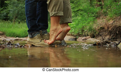 A young loving couple hugging and kissing. Two lovers, man and woman barefoot near the water.