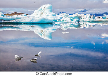 Ice splendor. Floating ice and clouds reflected in the...