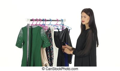 Women chooses some clothes at shop of fashinable clothes. White