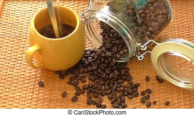 Yellow coffee cup and the cup is around coffee beans